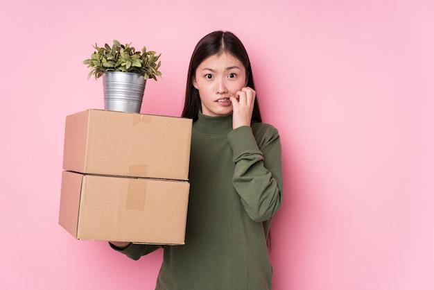 Молодая китайская женщина держа коробки изолировала кусая ногти, нервная и очень тревожная.