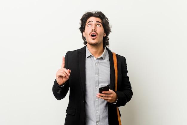 開いた口で逆さまに指している電話を保持している若いビジネスマン。