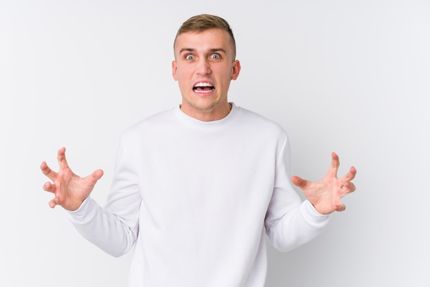 Молодой кавказский человек на белой стене кричащей с яростью.