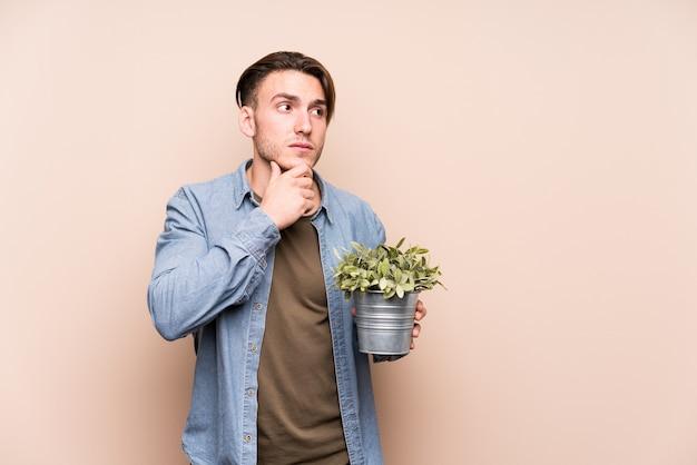 疑わしいと懐疑的な表情で横に見ている植物を保持している若い白人男。