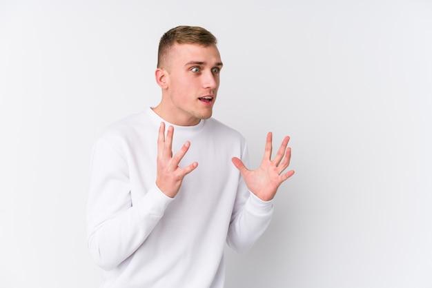 白い壁の若い白人男は大声で叫ぶ、目を開いたまま、手が緊張します。
