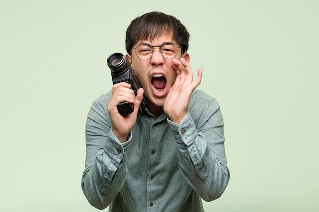前方に幸せな何かを叫ぶビンテージカメラを保持している若い中国人男性