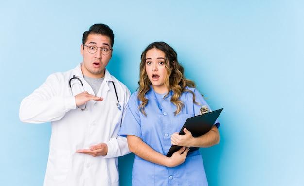 分離された青い壁でポーズをとる若い医者カップルはショックを受けて、手の間にコピースペースを保持してびっくりしました。