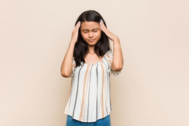 Молодой симпатичный китайский подросток молодая белокурая женщина, носящая пальто против храмов розовой стены, касающихся и имеющих головную боль.