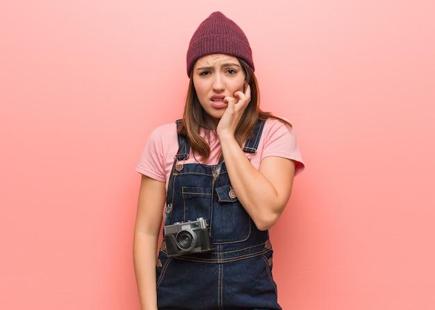 Молодой милый фотограф женщина кусает ногти, нервничает и очень беспокоится