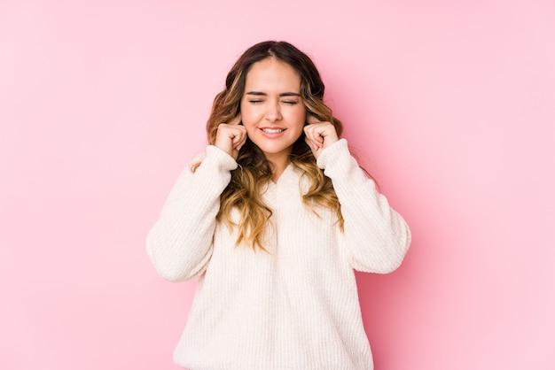 Молодая соблазнительная женщина позирует в розовой стене изолированы охватывающих уши руками.