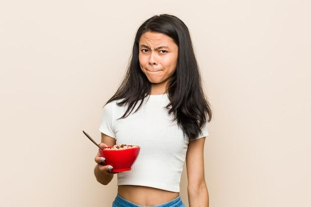 Молодая азиатская женщина держа шар хлопьев смущенный, чувствует сомнительным и неуверенным.