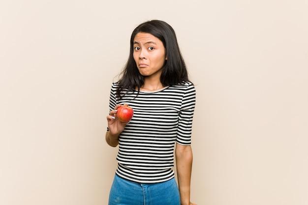 Молодая азиатская женщина держа яблоко пожимает плечами плечи и открытые глаза смущена.