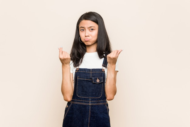 若いかわいい中国のティーンエイジャー彼女はお金がないことを示すピンクの壁にコートを着ている若いブロンドの女性。