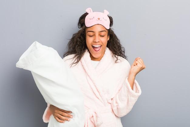 パジャマと屈託のない興奮を抱いて枕を保持している睡眠マスクを身に着けている若いアフリカ系アメリカ人女性。勝利のコンセプト。