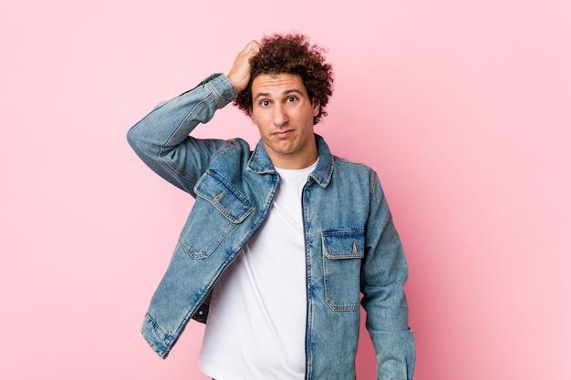 ショックを受けているピンクの壁にデニムジャケットを着ている巻き毛の成熟した男、彼女は重要な会議を覚えています。