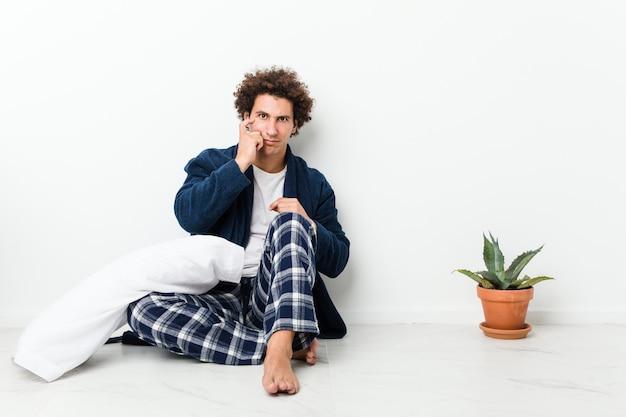 Пижама зрелого человека нося сидя на поле дома указывая висок с пальцем, думая, сфокусировала на задаче.