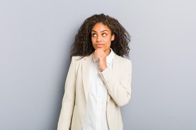 Молодая афро-американская бизнес-леди смотря косой с сомнительным и скептическим выражением.