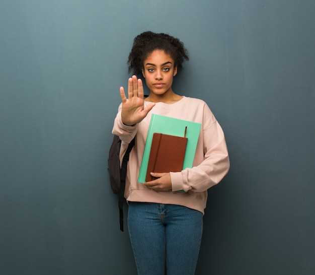 若い学生黒人女性が前に手を入れて。彼女は本を持っています。