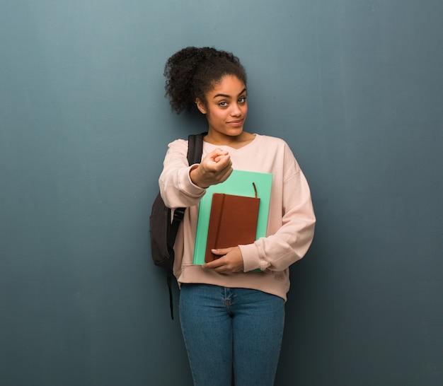 若い学生黒人女性が来て招待しています。彼女は本を持っています。