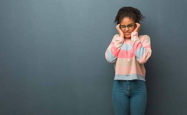 Молодая девушка афроамериканцев с голубыми глазами, охватывающих уши руками