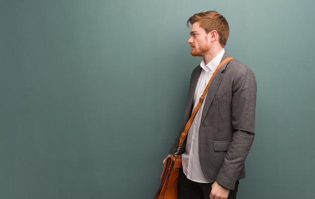 正面を向いている側に若い赤毛ビジネス男