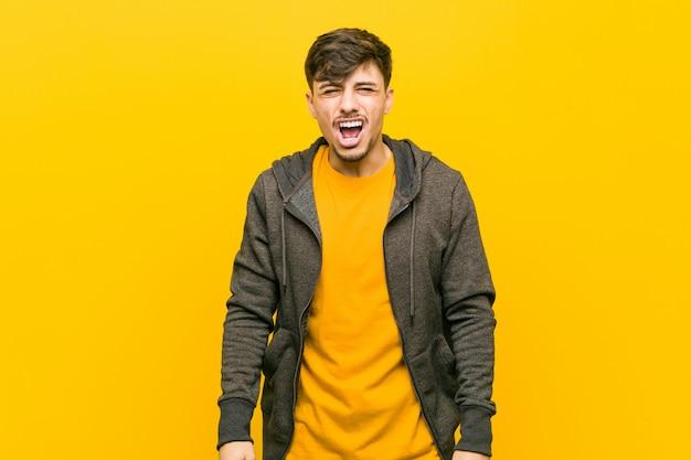 Молодой латиноамериканский случайный человек кричит очень злой и агрессивный.