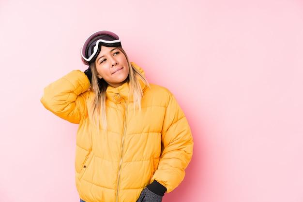 頭の後ろに触れるピンクの壁にスキー服を着て、考えて、選択をする若い白人女性。