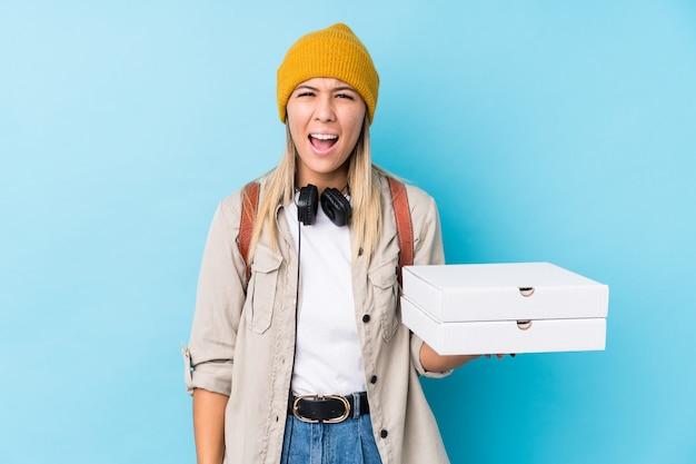 Молодая кавказская женщина держа пиццу изолировала кричащее очень сердитое и агрессивное.