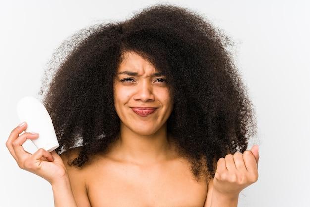Молодая афро женщина держа увлажнитель изолировала показ кулака к с агрессивным выражением лица.