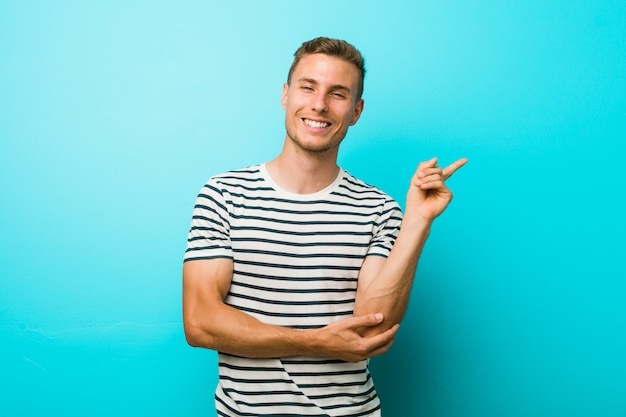 人差し指で元気に指している笑みを浮かべて青い壁に若い白人男。