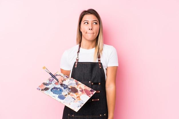 分離されたパレットを保持している若いアーティストの白人女性は混乱し、疑わしく不安を感じています。