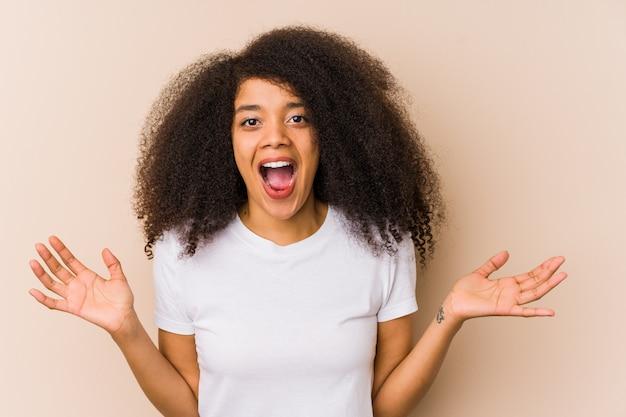 勝利や成功を祝う若いアフリカ系アメリカ人女性は、驚いてショックを受けています。