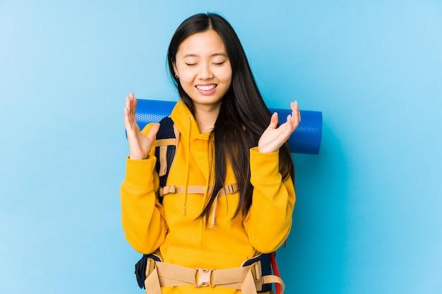 若い中国のバックパッカーの女性は、うれしそうな笑いをたくさん分離しました。幸福の概念。