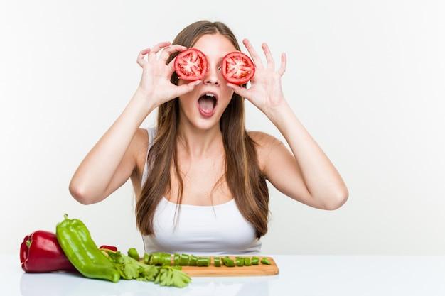 若い白人女性がトマトでポーズ