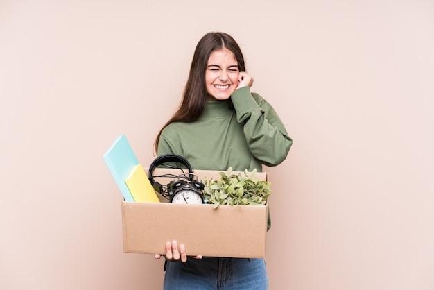 Молодая кавказская женщина двигая к новому дому изолировала покрывать уши руками.