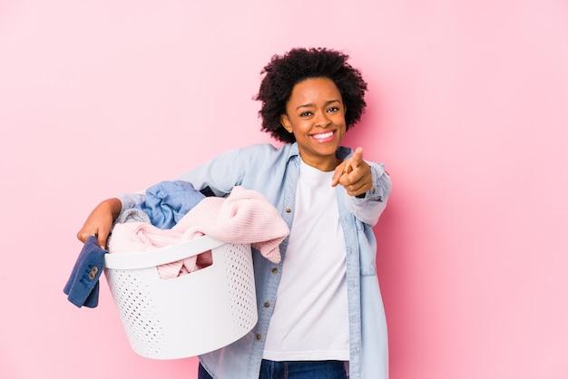Женщина среднего возраста афроамериканец делает прачечная изолированные веселые улыбки, указывая на фронт.