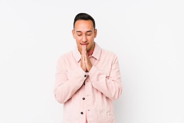 Молодой человек латинской позирует изолированные держаться за руки в молитве возле рта, чувствует себя уверенно.