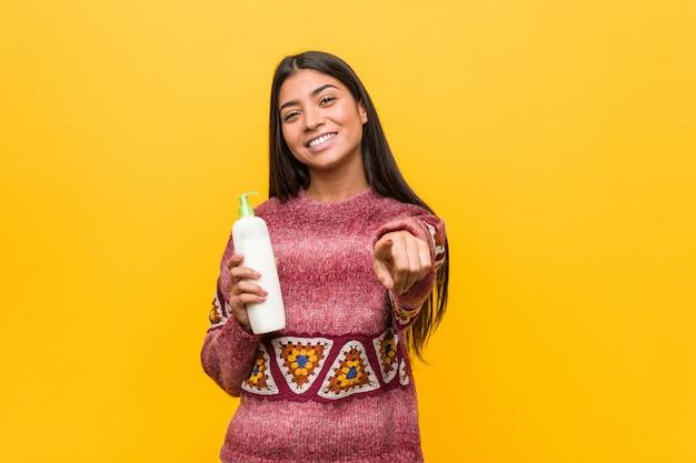 クリームボトルを保持している若いアラブ女性が正面を向く陽気な笑顔。