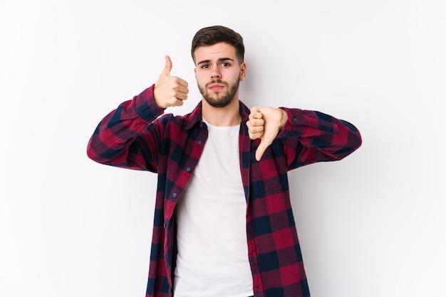 白い壁でポーズをとって親指を示す若い白人男