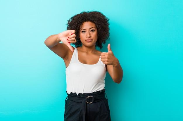 Молодая афро-американская женщина показывая большие пальцы руки вверх и большие пальцы руки вниз, трудная выбирает концепцию