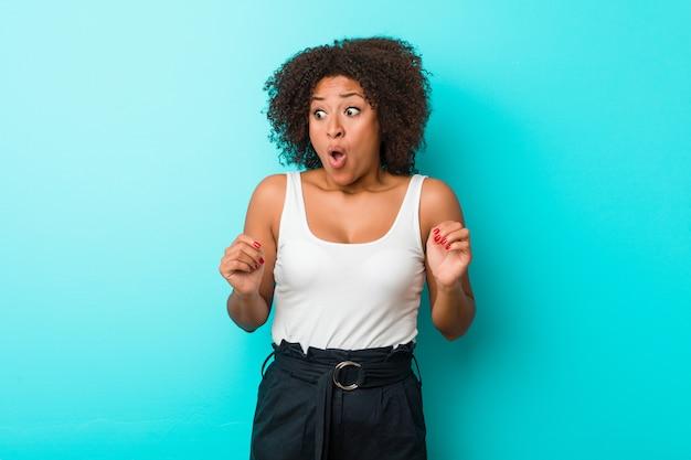 Молодая афро-американская женщина будучи шокированной из-за что-то она увидела.