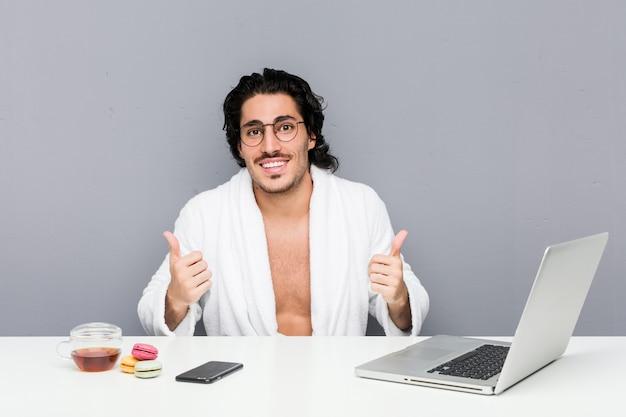 両方の親指を上げる、笑みを浮かべて、自信を持ってシャワーの後に働く若いハンサムな男。