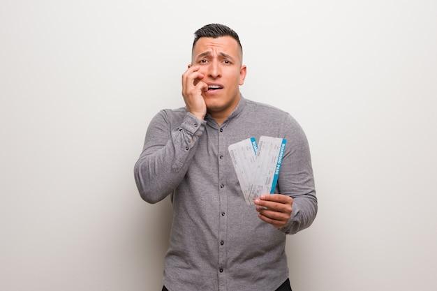 Молодой латинский мужчина держит авиабилеты, кусая ногти, нервный и очень взволнованный