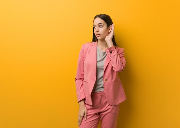 Молодая современная деловая женщина пытается слушать сплетни