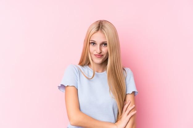 不機嫌そうな表情でカメラで見ている不幸なピンクの壁に若いブロンドの女性。