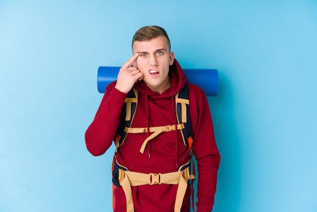 人差し指で失望のジェスチャーを示す若い旅行者白人男。