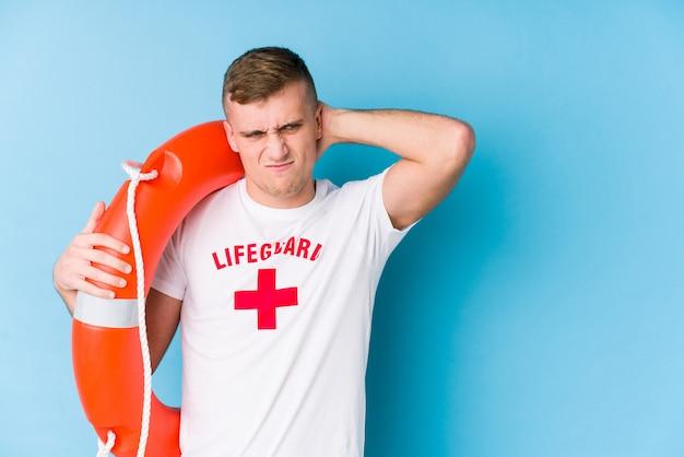 救助フロートを保持している若いライフガード男が頭の後ろに触れて、考えて、選択をします。