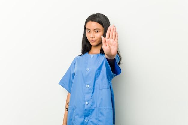 Молодая азиатская женщина медсестры стоя при протягиванный знак стопа показа руки, предотвращая вас.