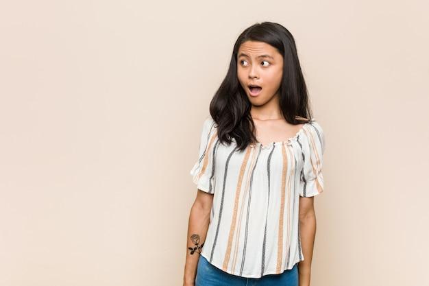 Молодой симпатичный китайский подросток молодая белокурая женщина в пальто против розовой стене шокированы из-за чего-то, что она видела.