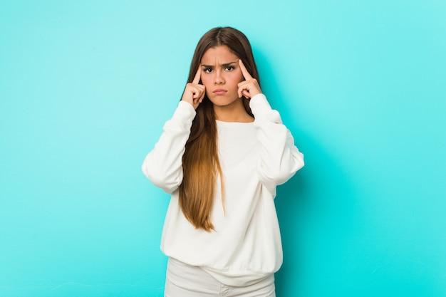 Молодая стройная женщина сосредоточилась на задаче, держа указательными пальцами указательную голову.