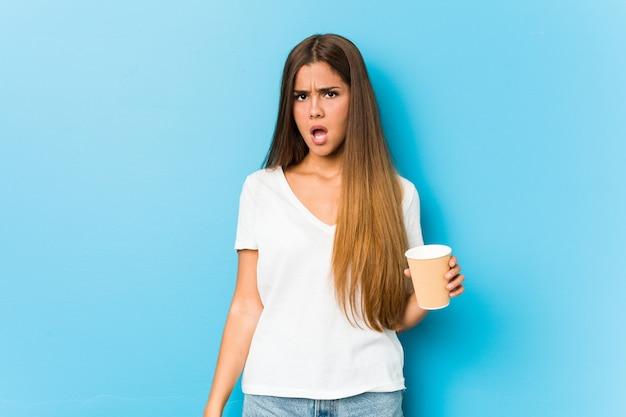Молодая милая кавказская женщина держа на вынос кофе кричащий очень сердитый и агрессивный.
