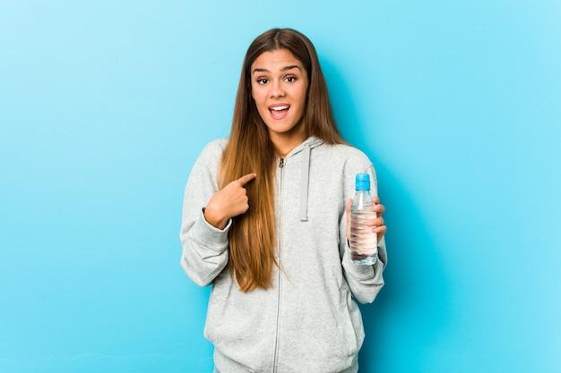 水のボトルを保持している若いフィットネス女性は、自分自身を指して驚いて、広く笑っています。