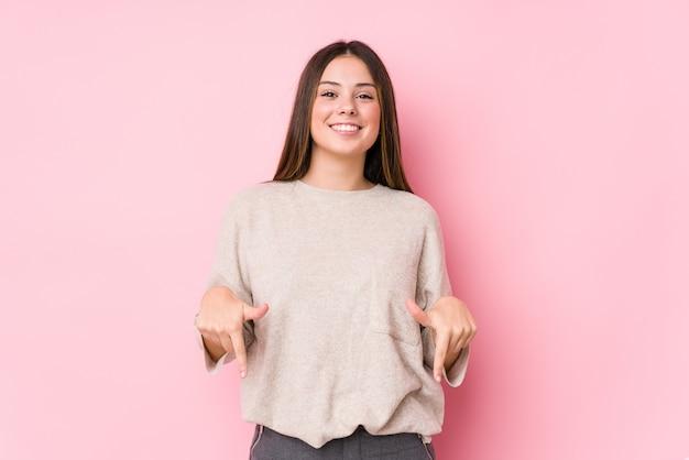 Молодая кавказская женщина представляя изолированные пункты вниз с пальцами, положительное чувство.