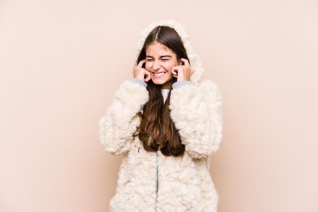 Молодая кавказская женщина представляя изолированные уши заволакивания руками.